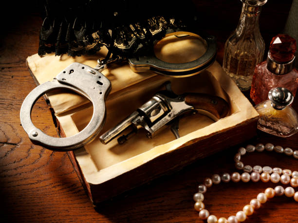 handcuffs and vintage gun - murder mystery stock photos and pictures