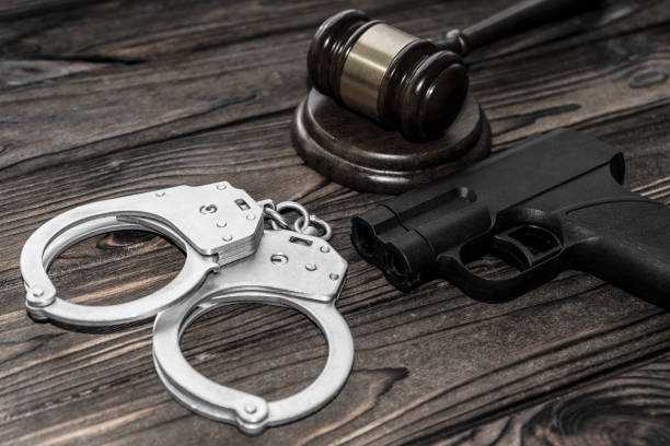 handcuffs for detaining criminals, a judge's hammer, a gun on a wooden background stock photo