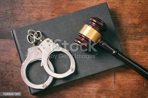 Law and order concept. Handcuffs, gavel on book on a wooden background, top view