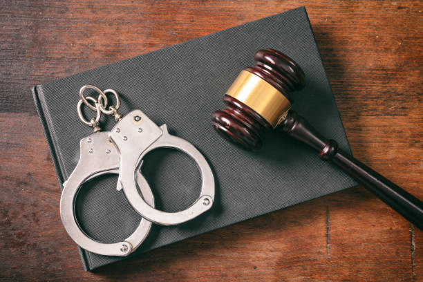 Handcuffs, gavel on book on a wooden background. Law and order concept. Handcuffs, gavel on book on a wooden background, top view analogue audio storage media stock pictures, royalty-free photos & images