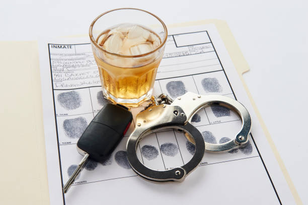 Handcuffs, keys and glass of alcohol on ice on top of finger print card stock photo