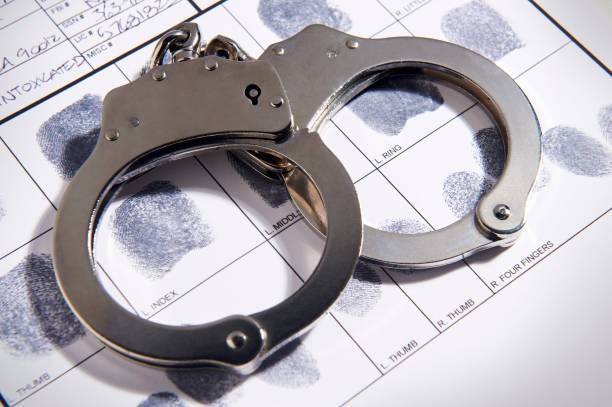 Handcuffs laying on top of fingerprint chart in file Handcuffs laying on top of fingerprint chart in file crime stock pictures, royalty-free photos & images