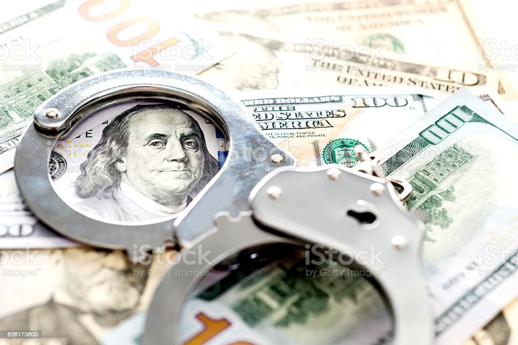 Handcuffs lying on american dollars stock photo