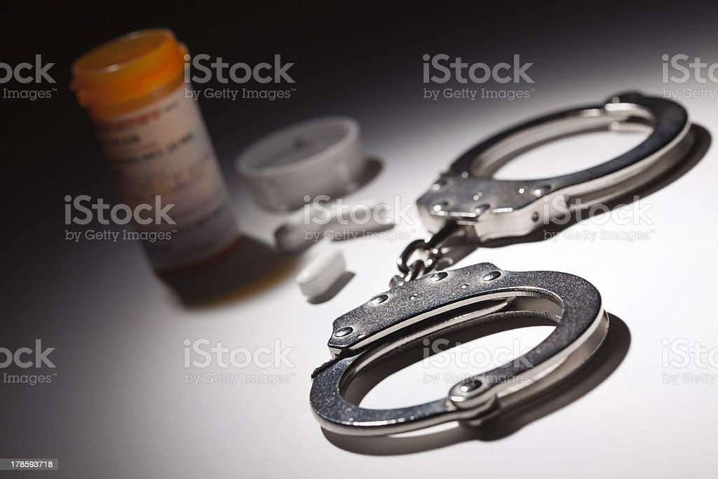 Handcuffs, Medicine Bottle and Pills Under Spot Light stock photo