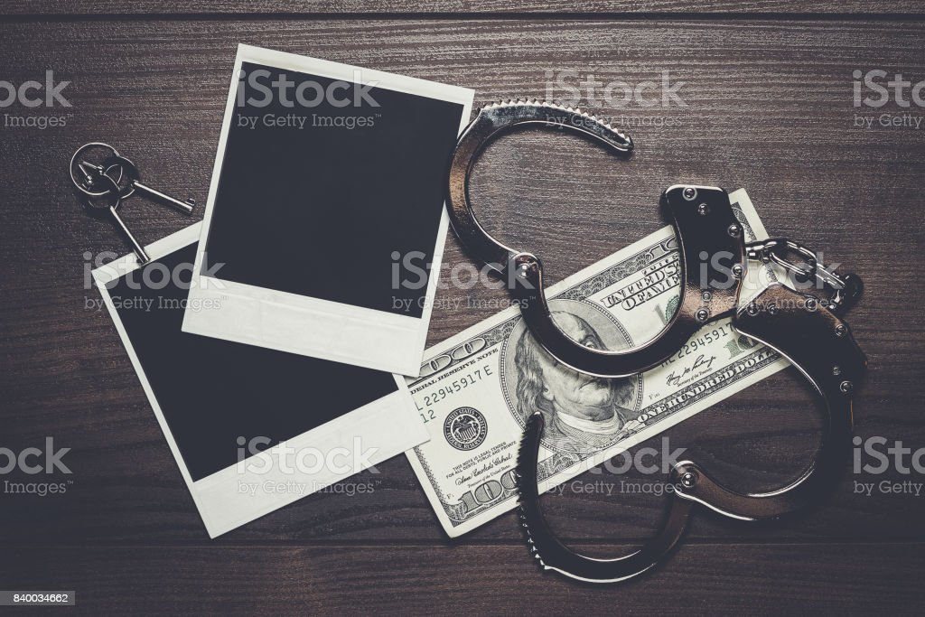 handcuffs money and old photos detective concept stock photo