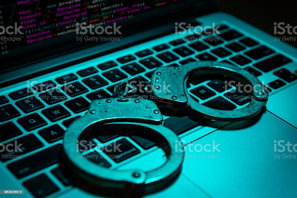 Handcuffs on Computer Keyboard - Royalty-free Arrest Stock Photo