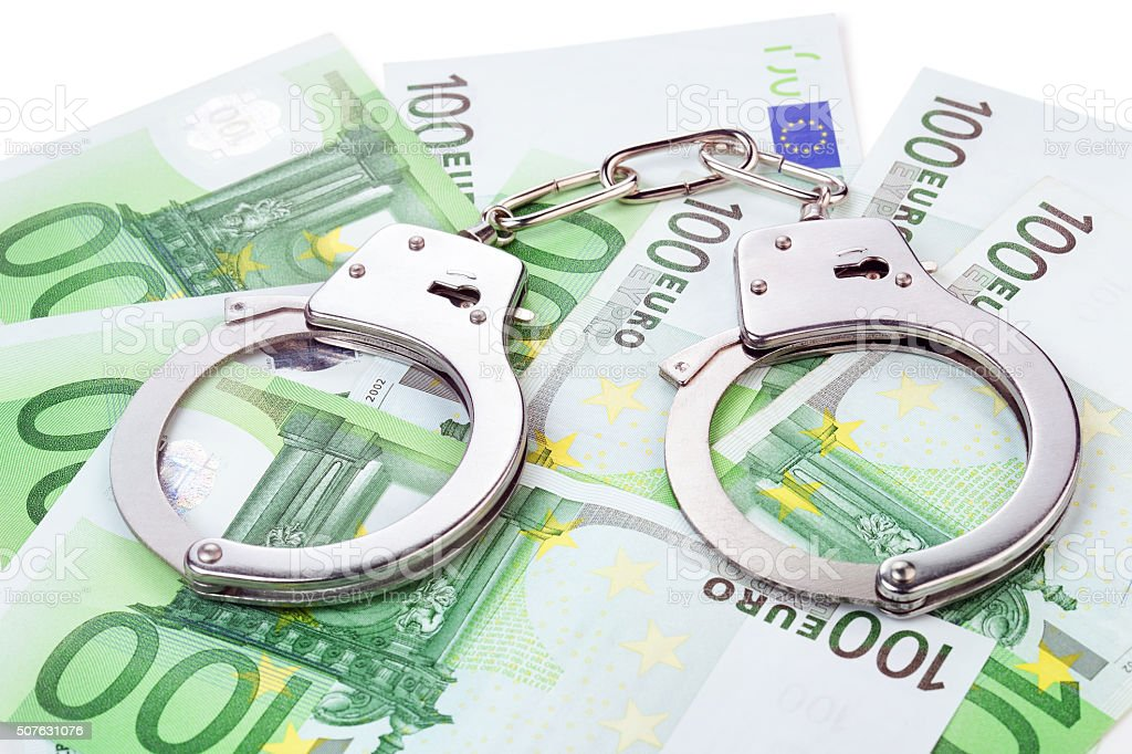 handcuffs on euro banknotes stock photo