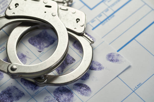 Handcuffs on fingerprints document stock photo
