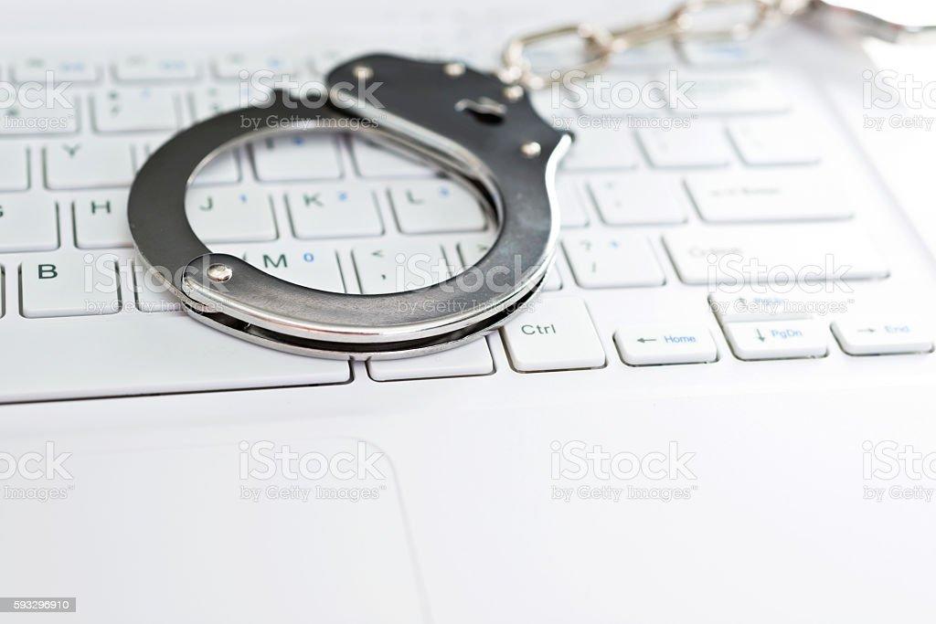Handcuffs on keyboard stock photo