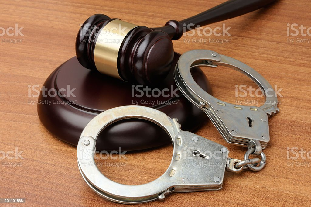 Handcuffs with gavel on a wood background stock photo