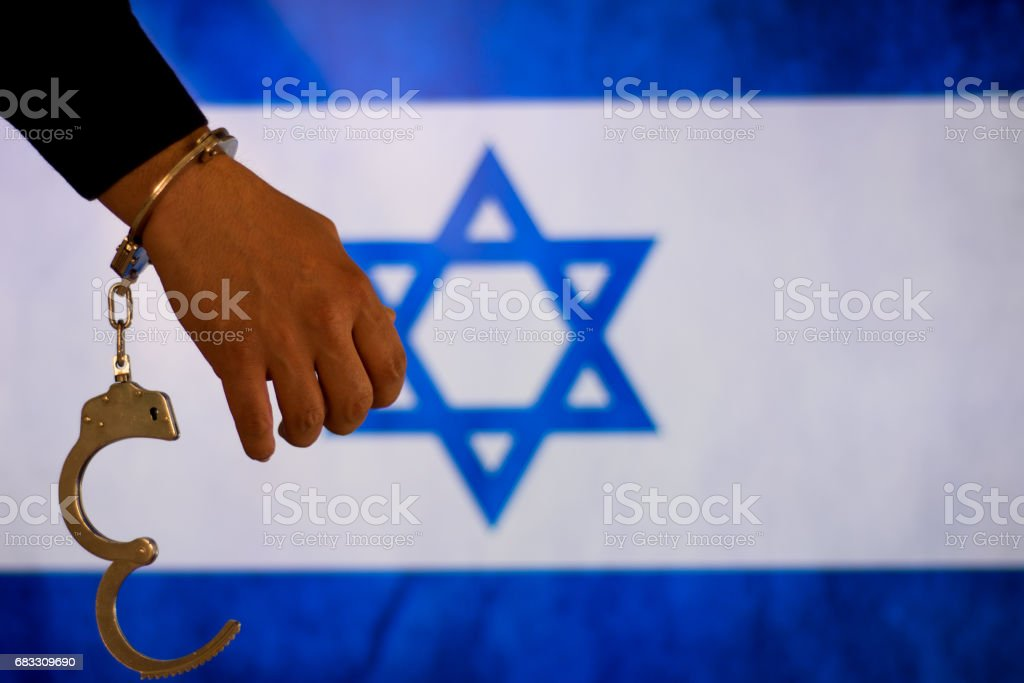 Handcuffs with hand in front of flag foto stock royalty-free