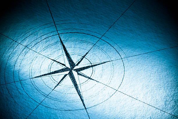 hand-drawn compass rose auf blauem papier - karte navigationsinstrument stock-fotos und bilder