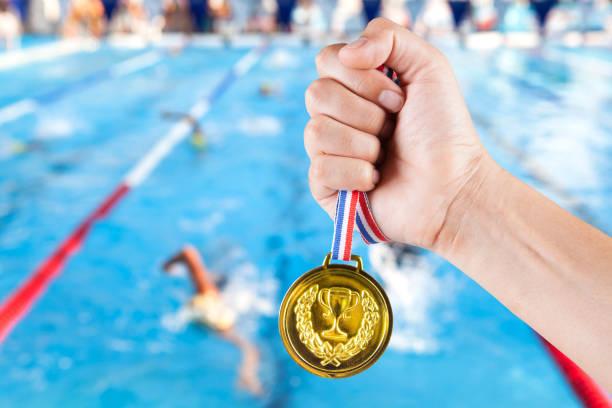 Handvoll asiatischen Mann mit Goldmedaille mit unscharfen Hintergrund Swimming Pool. – Foto