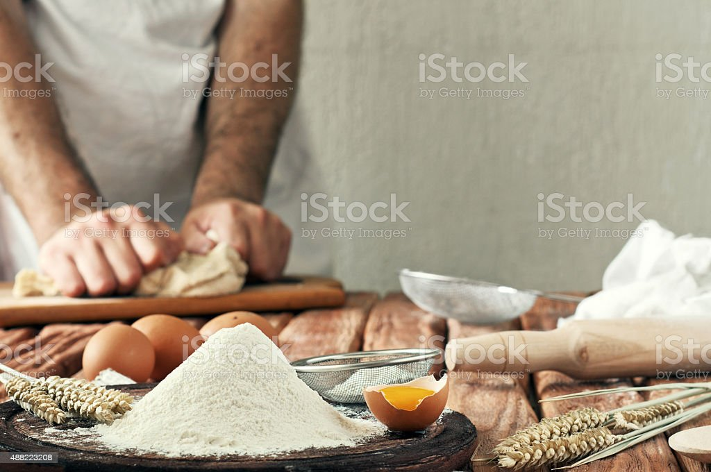 handful of flour with egg on a rustic kitchen stock photo