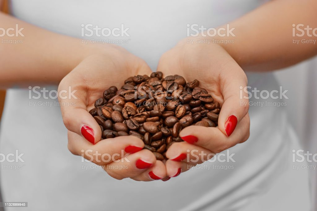 Handful of fresh organic coffee beans. Food and drink coffee...