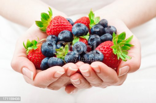 Woman holding a handful of fresh blueberries and strawberries. Horizontal framing, shallow depth of field used.