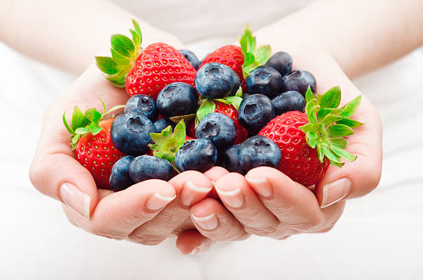 handful of fruits Woman holding a handful of fresh blueberries and strawberries. Horizontal framing, shallow depth of field used. handful stock pictures, royalty-free photos & images