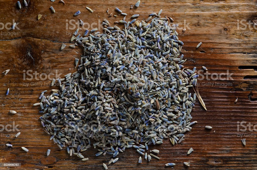 handful of lavender seeds on wood table stock photo