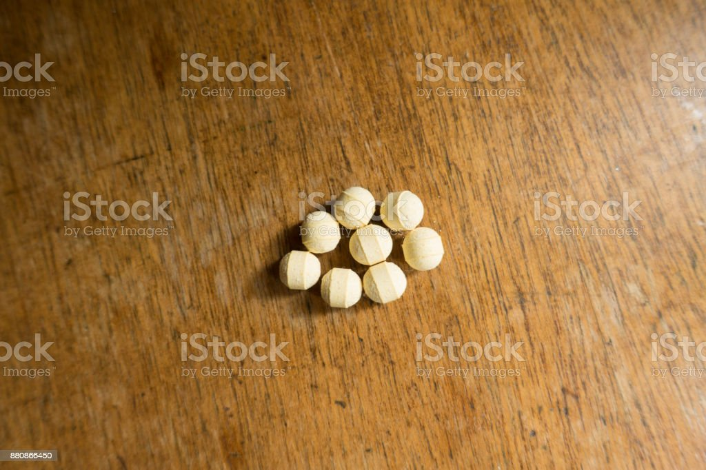 Handful of round probiotic tablets on wooden table stock photo