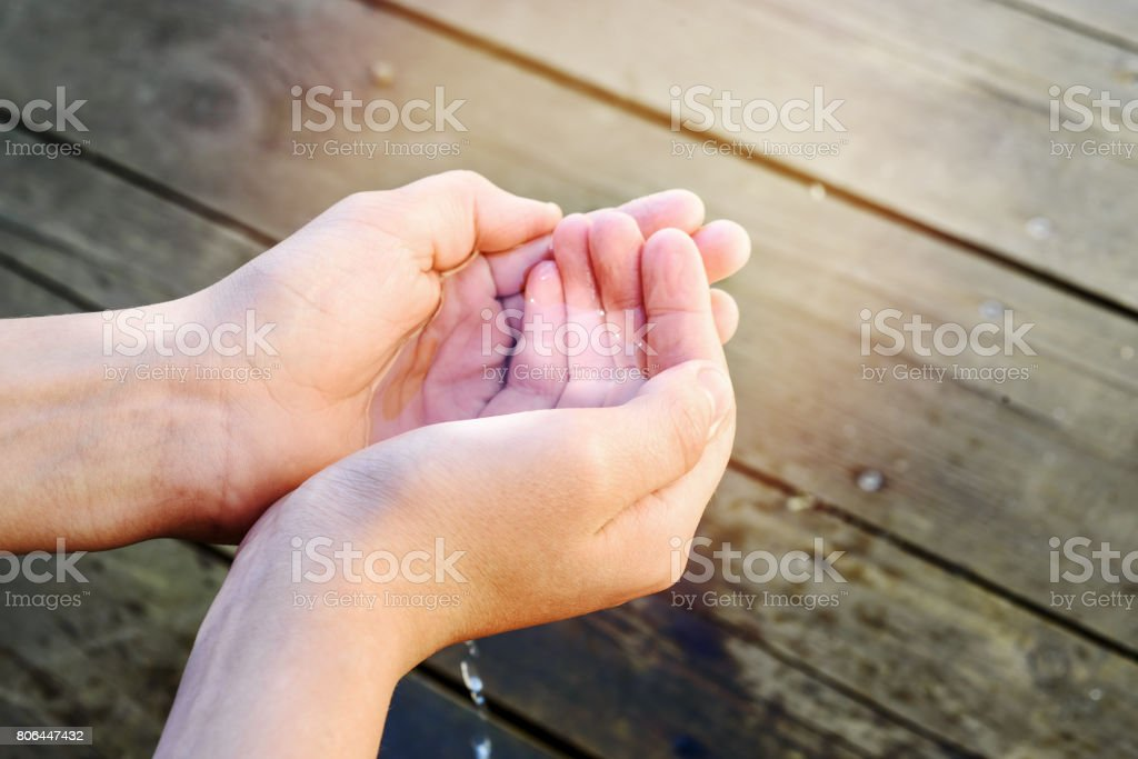 handful of water in the hands of a child stock photo