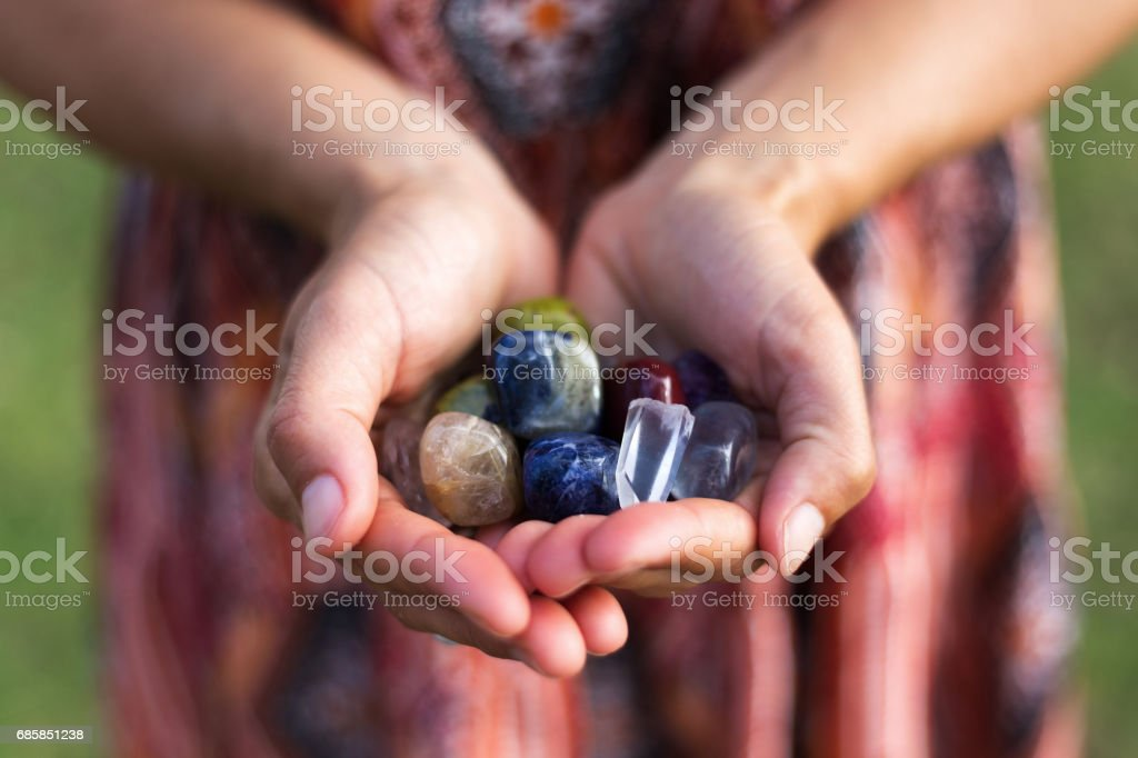 Handfull of Gemstones A young woman carefully holds a selection of vibrant gemstones as they reflect the soft sunlight. Adult Stock Photo