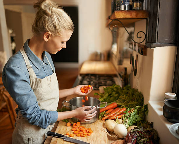 Handfuls of wholesome goodness Cropped shot of a woman cutting carrots on a cutting board stew stock pictures, royalty-free photos & images