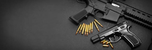 Handgun and rifle 9mm handgun with ar15 rifle and ammunition on dark background with copy space pistol stock pictures, royalty-free photos & images