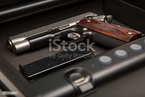 .45 caliber handgun and loaded clip sitting in a fingerprint safe box, ready to go in case it is needed.