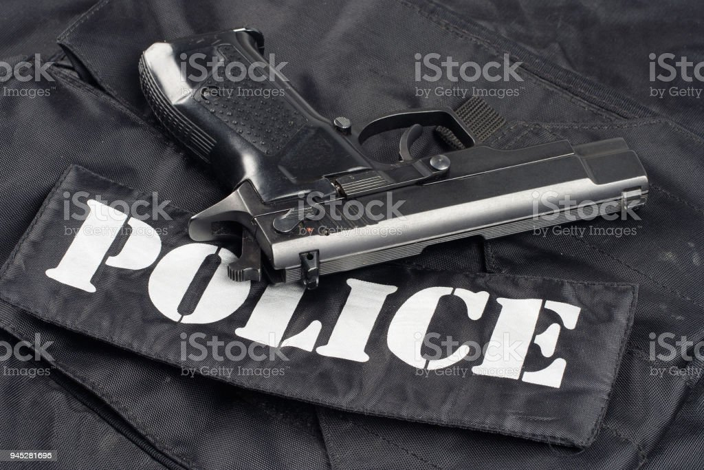 handgun on police black uniform background stock photo
