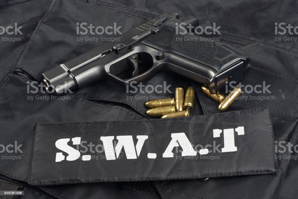 handgun on SWAT black uniform background stock photo