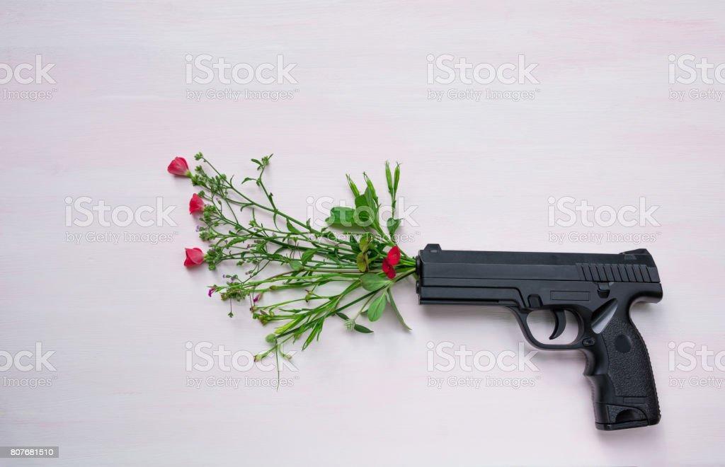 Pistole auf hölzernen Hintergrund mit Blumen. Krieg und Frieden voll mit Handfeuerwaffe. – Foto