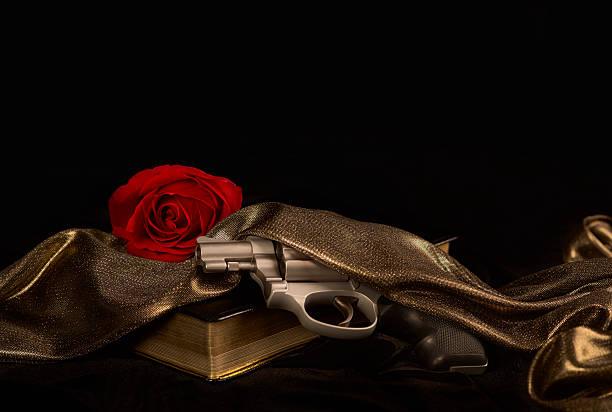 pistole auf einem buch mit einer roten rose - rosa tarnfarbe stock-fotos und bilder