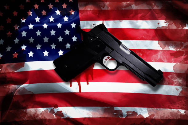 handgun with blood stain on American flag. reform gun control in America concept stock photo