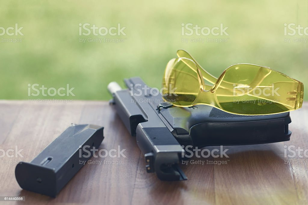 Handgun with safety glasses on a wooden background. stock photo