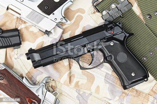 istock Handguns on camouflage background. 9mm Pistols. 602328498
