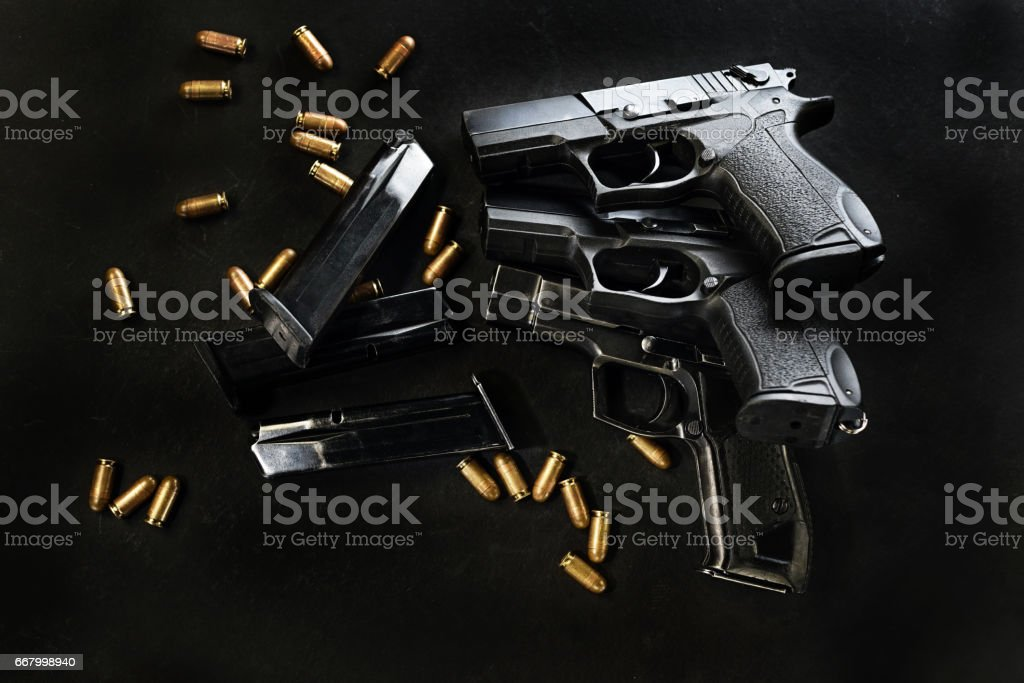 handguns with ammunition on a black surface stock photo