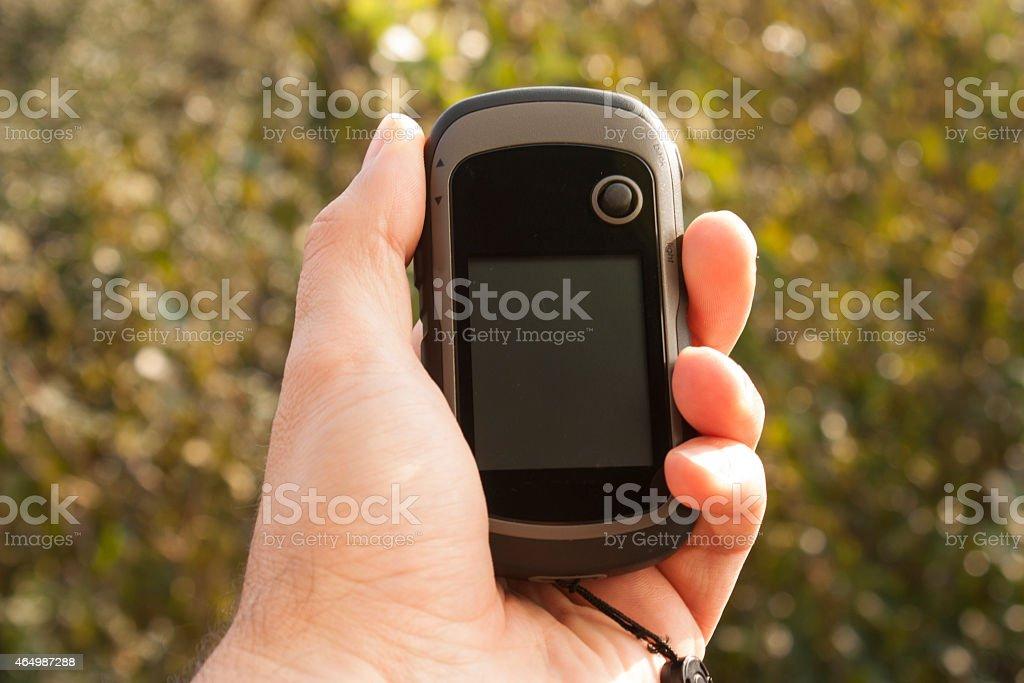 Handheld GPS transmiter in nahd on nature stock photo