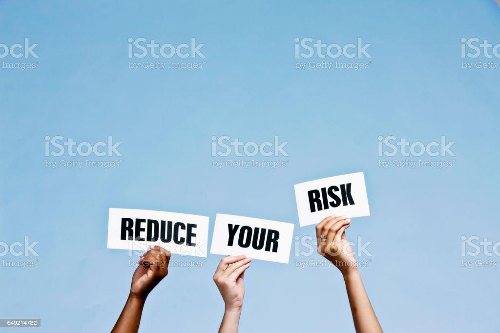 Panneaux à main lire «Réduire vos risques» contre le ciel bleu - Photo