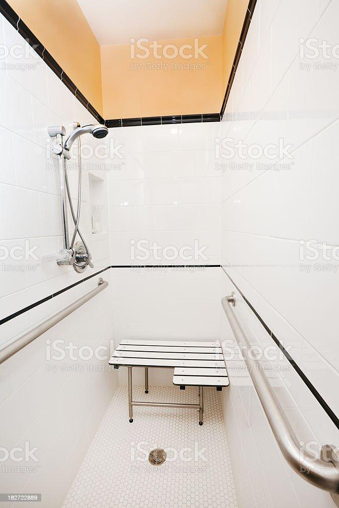 Behindertengerecht, geflieste Wand und Boden Dusche mit Haltestangen und Sitz – Foto