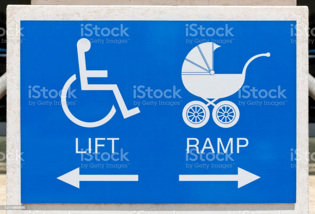 Handicap and baby stroller sign on a building giving direction stock photo