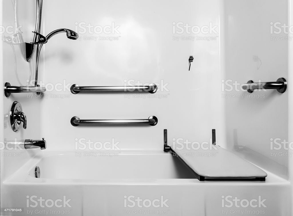 Handicap Bath The fold down seat helps the disabled and handicap use the shower easier with access at the height of a wheelchair. The adjustable shower handle allows multiple heights for use. The wall handles help with accessibility.  Accessibility Stock Photo
