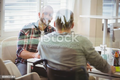 660681964istockphoto Handicap businessman discussing with colleague in office 658902064