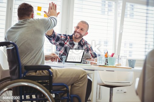 660681964istockphoto Handicap businessman giving high-five to colleague in office 658902000