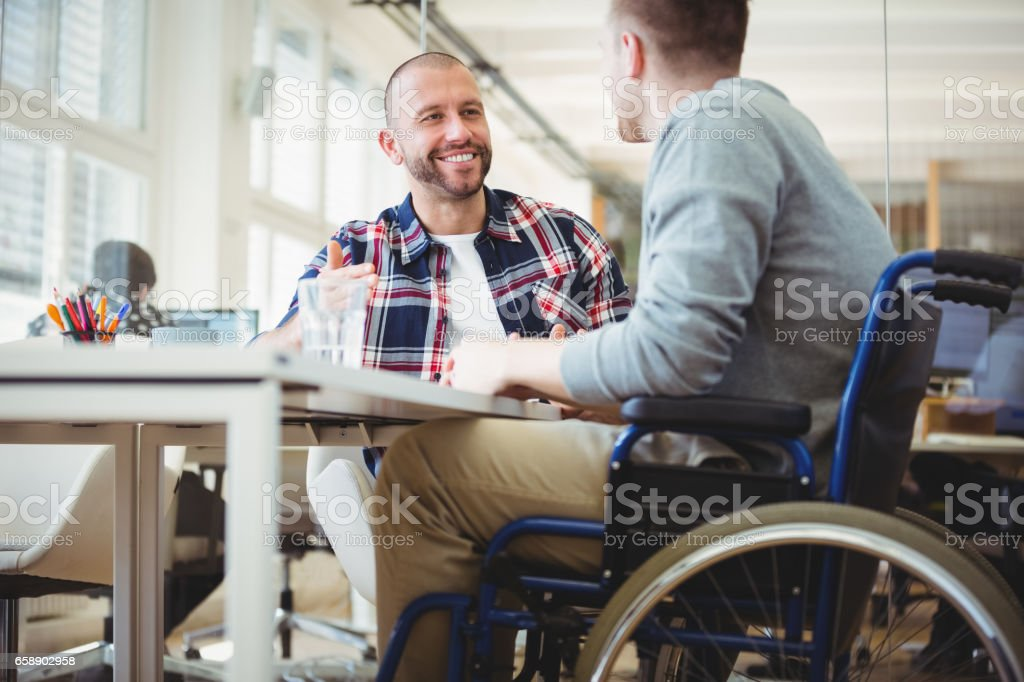 Handicap businessman sitting with colleague in office stock photo