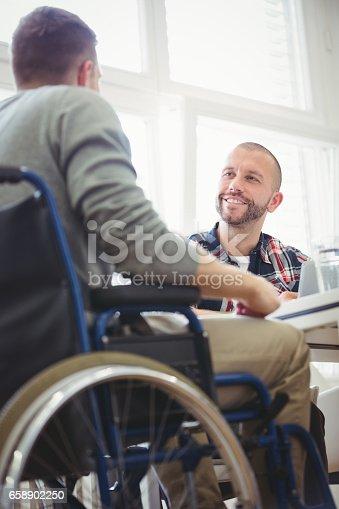 660681964istockphoto Handicap businessman with colleague in creative office 658902250