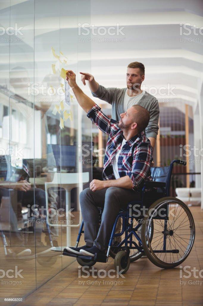 Handicap-Geschäftsmann mit Kollegen kleben Klebefuge Notizen im Büro – Foto