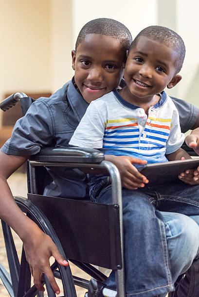 Handicap child playing with his little brother Black Smiling Handicap child playing with his little brother haitian ethnicity stock pictures, royalty-free photos & images