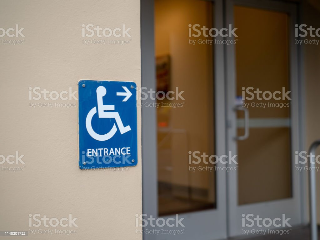 Handicap entrance sign pointing to right in front of a office door
