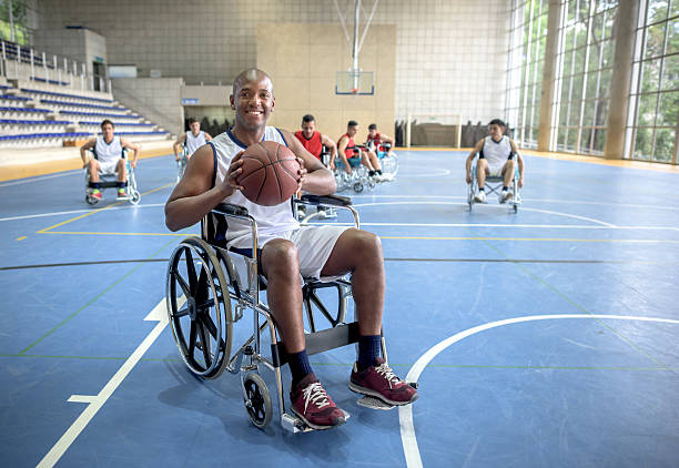 handicap man playing basket - sports en fauteuil roulant photos et images de collection