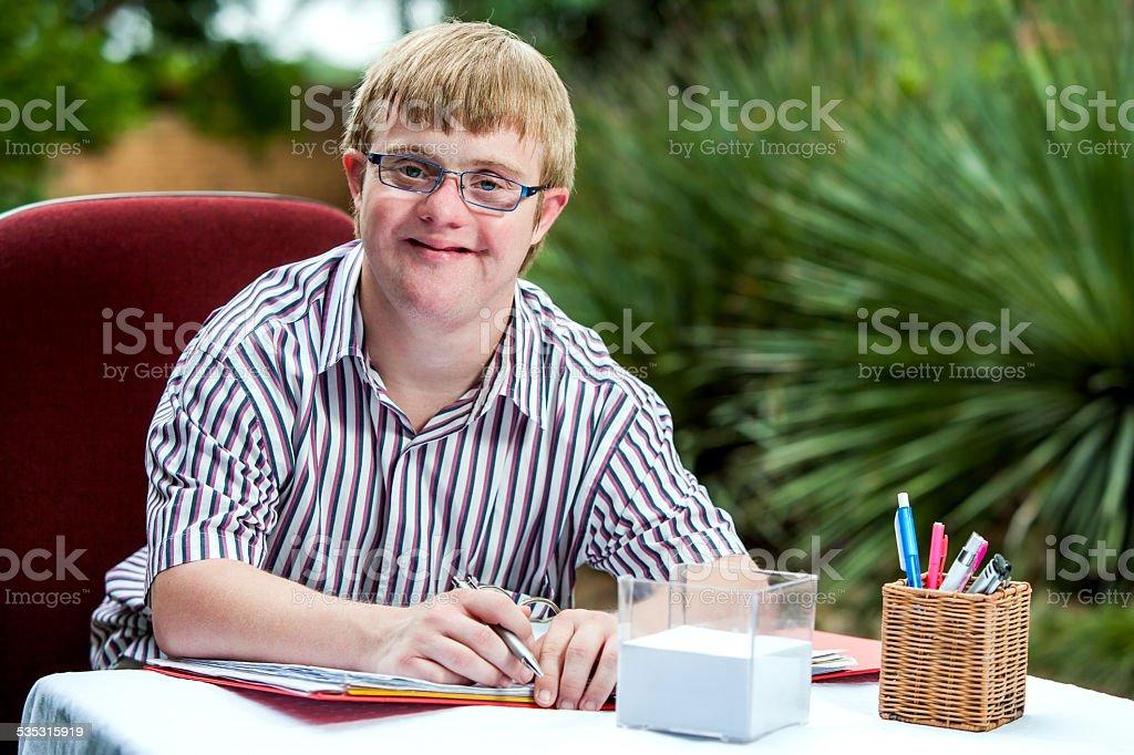 Handicapped boy at desk in garden. stock photo